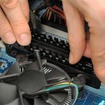 Technician's hands installing user memory on a computer mainboard